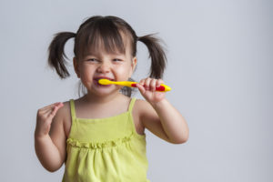 little girl smiling and brushing teeth