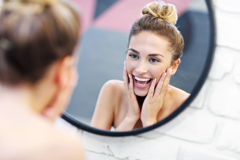 Person with beautiful smile from emergency dentist in Wharton looking in mirror