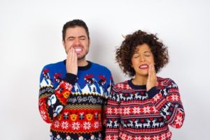 Man and woman wearing seasonal sweaters and holding one side of their mouths in pain
